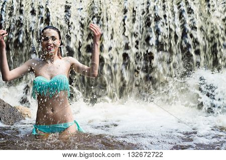 beautiful woman splashes water on waterfall outdoors