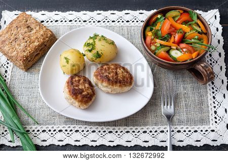 Cutlets home with boiled potatoes and dill salad with fresh vegetables and grain bread on a rustic napkin on a wooden surface