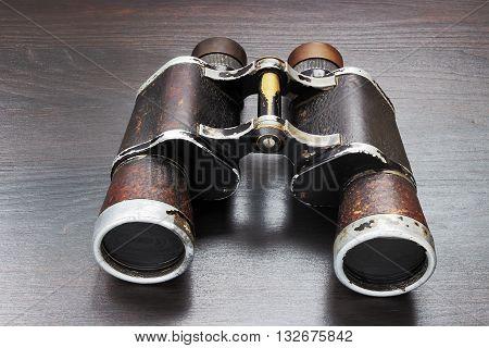 Old field binoculars on a wooden background