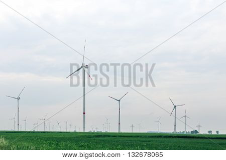 Ecological alternative power with windmill on the green field.Windmill generator in wide yard. Yard of windmill power generator under blue sky, shown as energy industry concept.