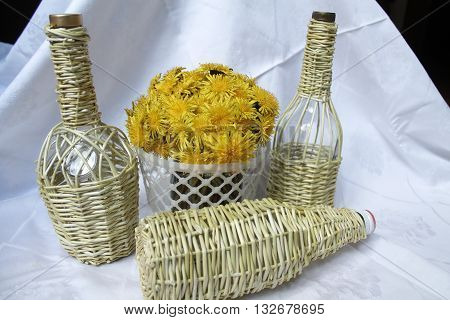bottle weaves rods for save wine and brandy with bouquet of yellow dandelion