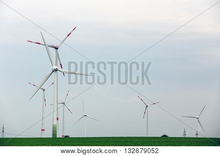 Ecological power with windmill on the field.Yard of windmill power generatorunder blue sky, shown as energy industry concept.Wind turbines generating electricity.