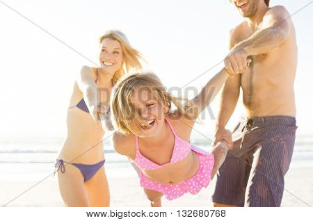 Father and mother playing with daughter on the beach. Joyful little girl with her parents playing at beach. Family enjoy summer vacation on the beach.