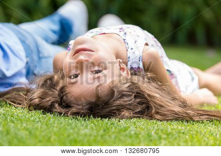 Little girl lying on grass and smiling. Close up of a smiling cute child lying besides father in park. Happy little girl lying on back with her head upside down looking at camera.