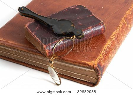Antique two books and lorgnette from 19th century on white background