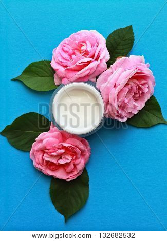 open cosmetic face cream and roses on blue background flat lay composition with copy space