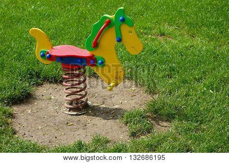children's rocking horse on a green grass