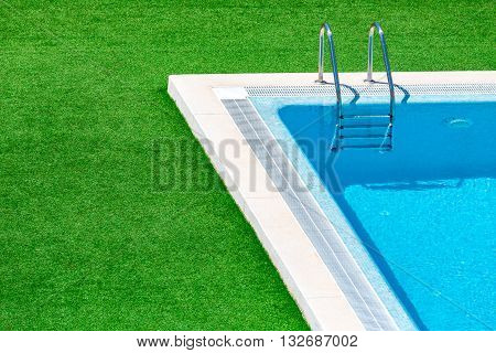 Swimming pool with stair in hotel pool resort.Swimming pool with blue spa swimming pool with clean water.Beautiful swimming pool with green grass around.