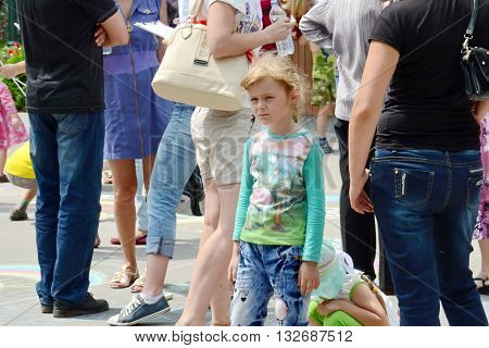 KHARKOV UKRAINE - 20 JUNE 2015: World Refugee Day observed in Kharkov Ukraine. A girl who escaped war in the East of Ukraine looking lonely.