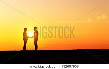 Businesspeolpe silhouettes shaking hands at sunset on lanscape background
