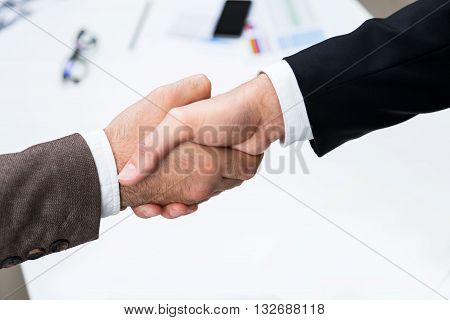 Top view of businesspeople shaking hands above office desktop with blurry items