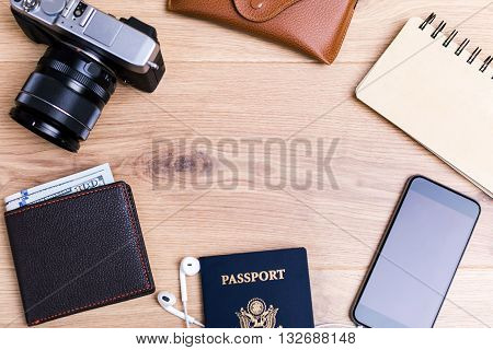 Traveling concept with american passport blank smart phone camera and other items on wooden desktop. Top view Mock up