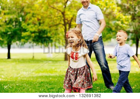 Playful little girl in park with his brother and father behind her out of focus.