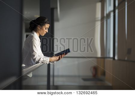 Strong confident business woman standing in an office building holding a note pad preparing for a meeting