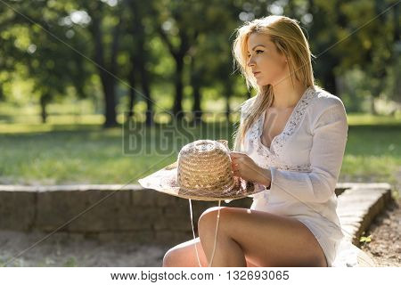 Beautiful blond enjoying in the park on a sunny summer day sitting on a brick wall beneath the tree and holding a hat