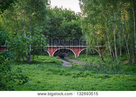 Red arched bridge through a stony ravine in city park