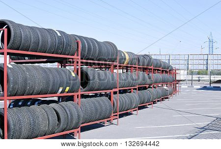 MOSCOW, RUSSIA - MAY 9, 2016: Many rubber tires on a rack on a sunny day