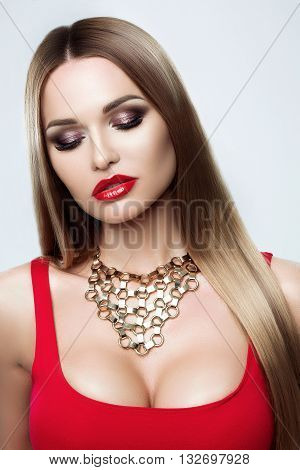 Beauty portrait of a gorgeous young woman with a healthy light brown hair, dark evening makeup, red full lips, large gold jewelry, gorgeous Breasts, red dress