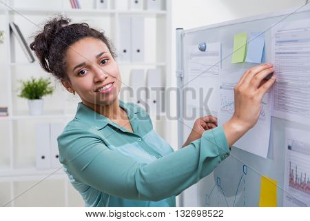 Smiling african american woman in office next to whiteboard with sticker memos and printed business charts