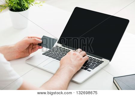 Online shopping concept with man's hands copying information from credit card to laptop with blank screen on white desktop. Mock up