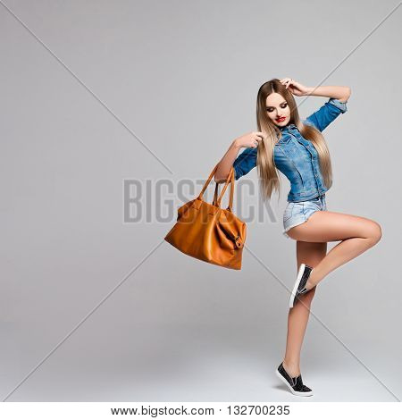 Beautiful girl in motion in a denim outfit with a large orange bag in her hand. Fashionable woman with long hair and legs. Advertising, catalog, beauty, space