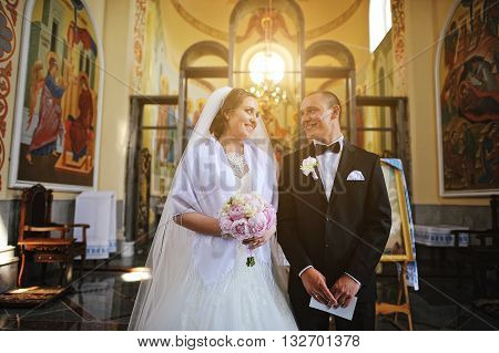 Happy Wedding Couple Stay At Church And Looked Each Other At Sunbeam