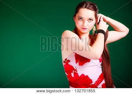 Leisure and lifestyle concept. Young woman in summer flowery dress on green background. Fashion photo.