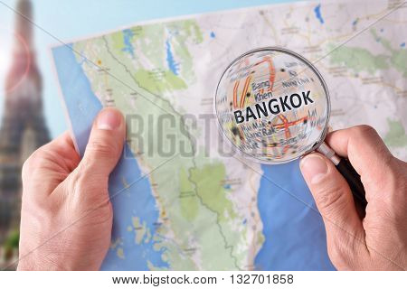 Man Consulting A Map Of Bangkok With A Magnifying Glass