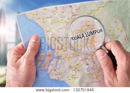 Man Consulting A Map Of Kuala Lumpur With Magnifying Glass