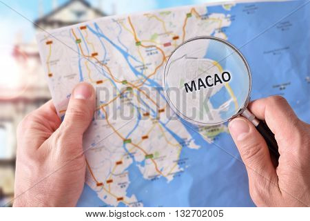 Man Consulting A Map Of Macao With A Magnifying Glass