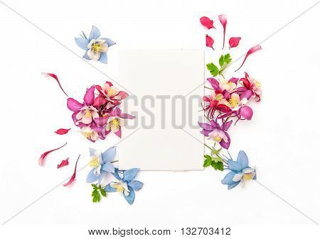 Columbines flower frame with empty sketchbook. Flat lay background