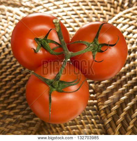 A CLUSTER OF THREE CHERRY TOMATOES ON A MATTING BACKGROUND