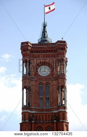 BERLIN, GERMANY - MAY 09: The historic tower of the Red Town Hall in Berlin's Mitte district with the Berlin flag on the spire on May 09, 2016 in Berlin.