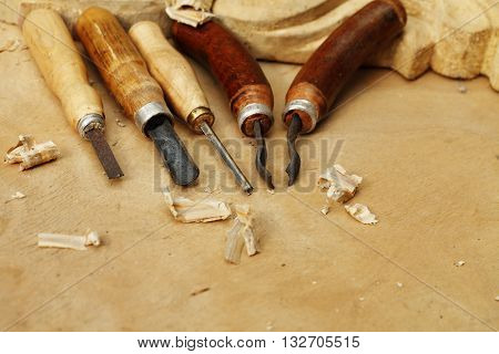 Vintage tools of woodcarving closeup on wooden background