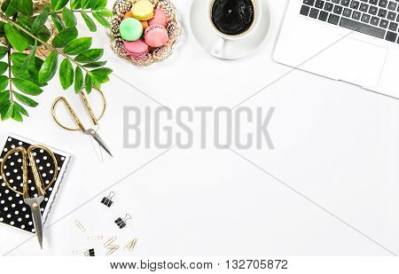 Feminine office table with coffee cookies laptop computer and green plant on white table background. Flat lay