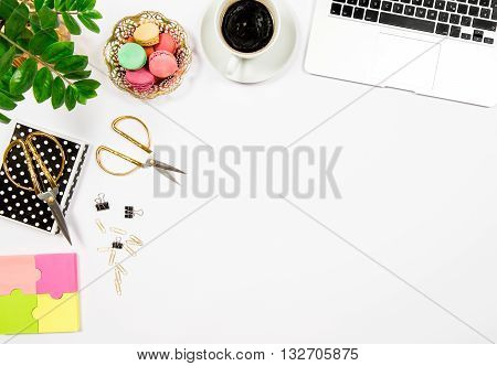 Feminine office desk workplace. Coffee cookies laptop computer and gren plant on white table background. Top view. Flat lay