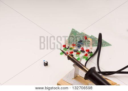 set of radio-electronic details of different color and soldering iron on a white background