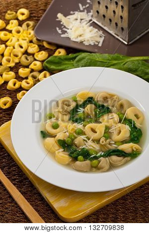 Italian Tortellini Pasta Soup with Peas and Spinach. Selective focus.