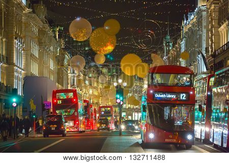 LONDON, UK - DECEMBER 30, 2015: Christmas lights decoration at Regent street and lots of people walking during the Christmas sale and public transport, buses and taxies