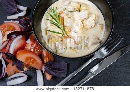 Braise fillet slices of turkey, chicken in a creamy sauce with vegetables. Black background.