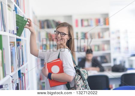 smart looking famale student girl  in collage school library selecting book to read