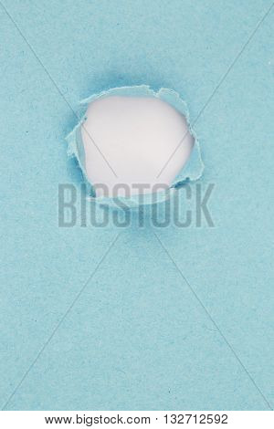 High resolution photography of hole in blue paper - visible paper texture