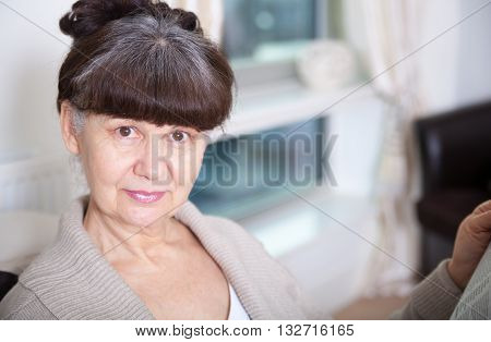 Pension age good looking woman smiling portrait in domestic environment
