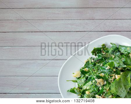 Vegetarian food in white dish on wood table. Stir fried Gnetum gnemon or Melinjo with egg in white plate isolated on white background. Thai local traditional food.