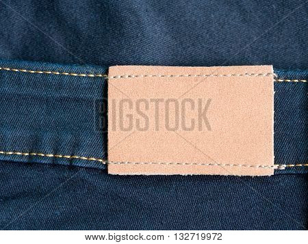 Empty brown leather tag with jean and seam in background. Highly detailed closeup of blank leather label tag on blue jeans.