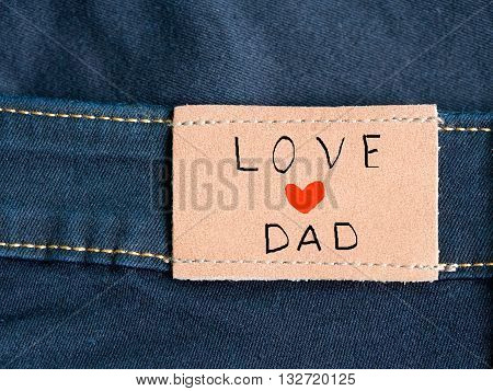 Love dad. Happy Father's Day celebrations. Love dad with red heart shape written on brown tag of blue jean. Father's day.