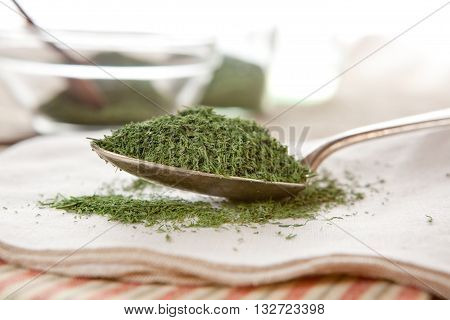 Dried dill in kitchen on a spoon