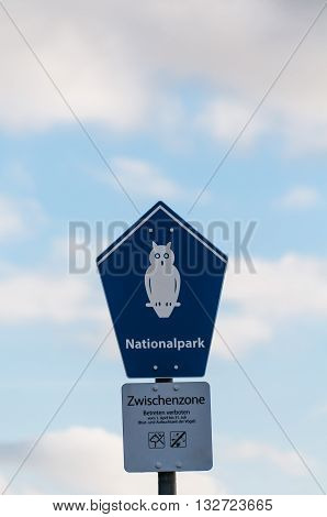 A sign with a bird, owl on it that says: National Park, do not enter in front of blue sky with some clouds