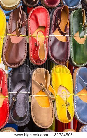 Multicolored comfortable leather shoes on sale on stall at the bazaar on the street