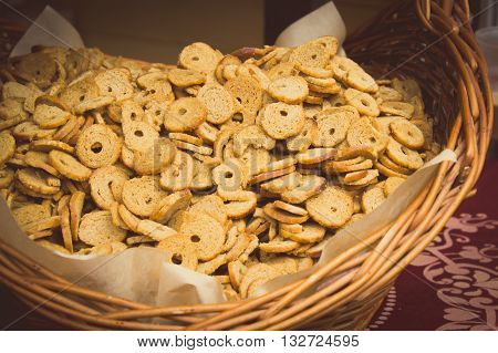 Vintage photo Fresh baked bagel chips in wicker basket on stall at the bazaar